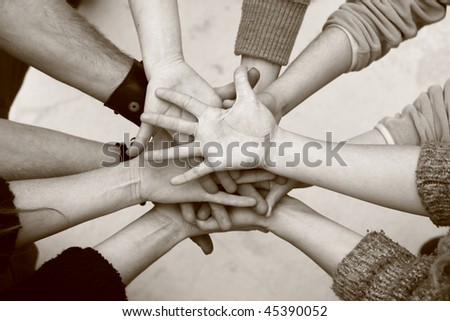 Five people join their hands together - stock photo