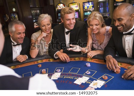 Five people sitting around blackjack table in casino - stock photo