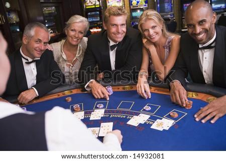 Five people sitting around blackjack table in casino - stock photo