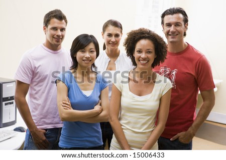 Five people standing in computer room smiling - stock photo
