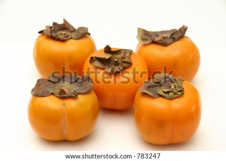 Five persimmons arranged as on dice, on a white surface and background - stock photo