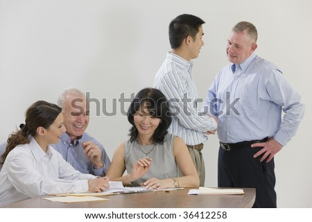 Five person business meeting with handshaking.