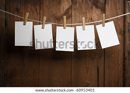 five photo paper attach to rope with clothes pins on wooden background