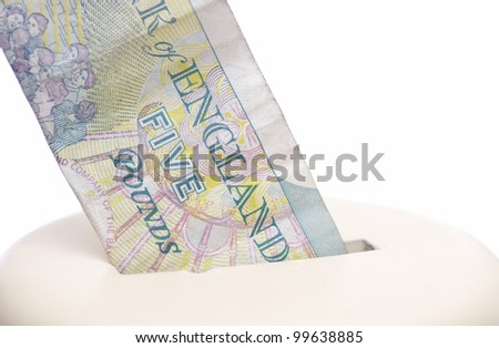 Five pound note being placed into a piggy bank. - stock photo