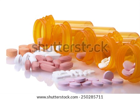 Five Prescription bottles lined up on their sides spilling medication pills out onto a reflective surface isolated on a white background. Depicting multiple medications, overwhelming to keep track of - stock photo