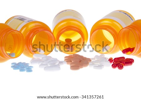 Five Prescription bottles lined up on their sides spilling medication pills out onto a white table surface isolated on a white background. Depicting multiple medications, overwhelming to keep track of - stock photo