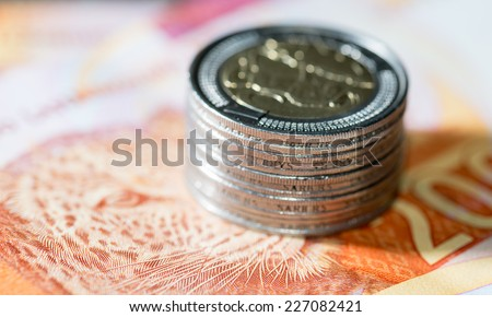 Five rand coins on a two hundred rand note 9
