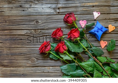 Five red and green stemmed roses and four little heart shapes resting on top of old wooden background - stock photo
