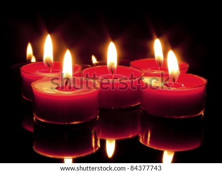 Five red candles on a black, reflective background