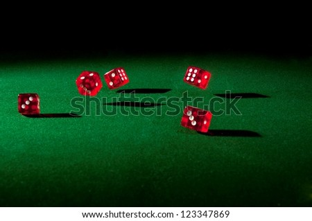 Five red dice rolling on the table with hard shadows - stock photo
