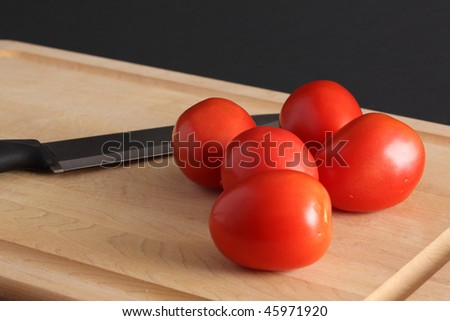 Five red Roma tomatoes on a wooden cutting board with a sharp knife against a black background - stock photo