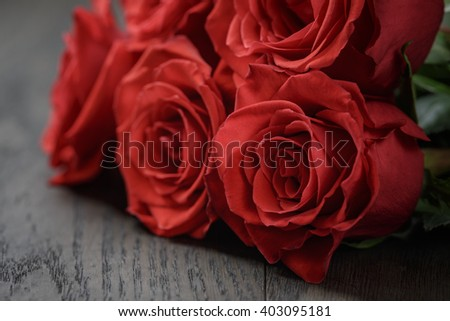 five red roses on wooden table, shallow focus