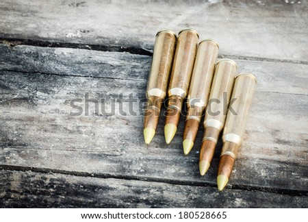 five rifle bullets on old wood desk - stock photo