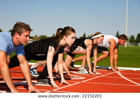 Five runners lined up ready to race.  Selective focus on second runner. - stock photo