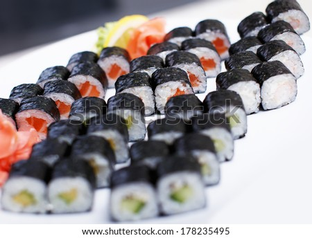 Five sets of different sushi on a big white plate - stock photo