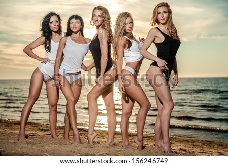 Five sexy ladies posing on the beach at sunset - stock photo