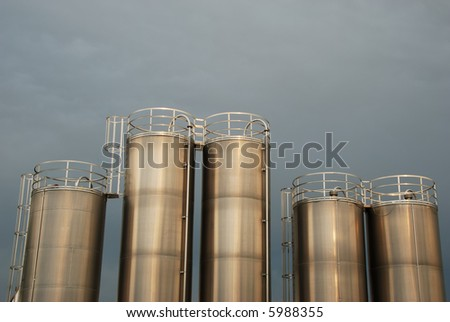 Five silver silos in front of a grey sky