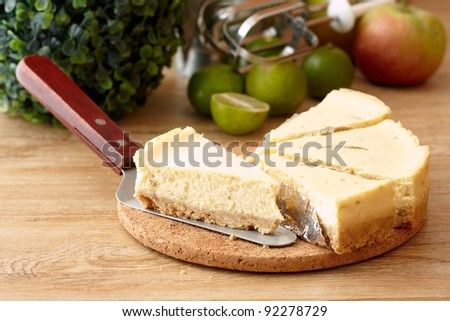 Five slices of New York Cheesecake on cork plate with limes, apple and a small green tree One of New York Cheesecake is on a cake server. - stock photo