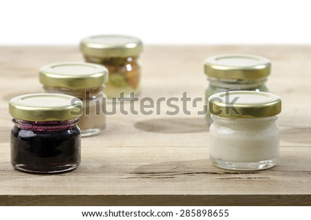 Five small jars of honey of different flavors: almond, blackberry - stock photo
