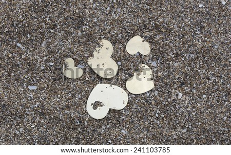 Five small metallic heart shapes are placed on dark sand background. - stock photo
