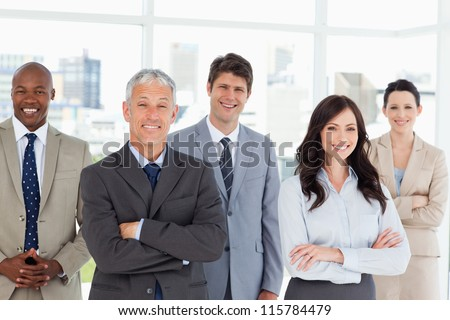 Five smiling business people crossing their arms in front of a bright window