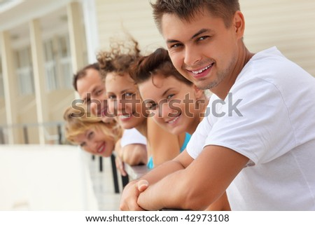 Five smiling friends on balcony - stock photo