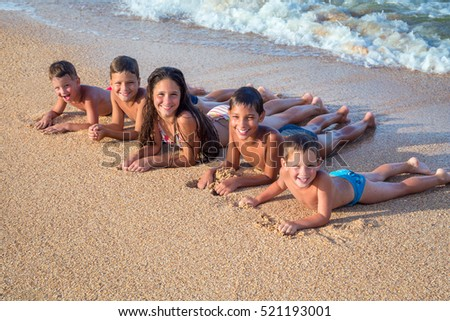 Five smiling happy kids lying down on the beach near water
