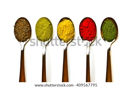 Five spices in metal teaspoons isolated on white with space for copy. - stock photo
