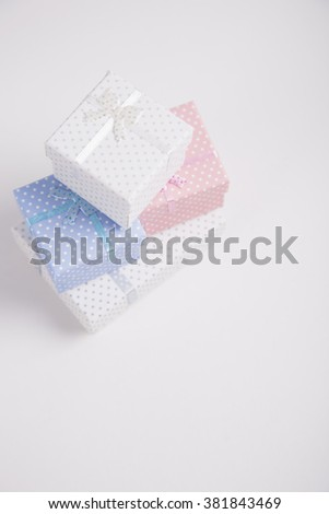Five spotted squared gift boxes on white background.