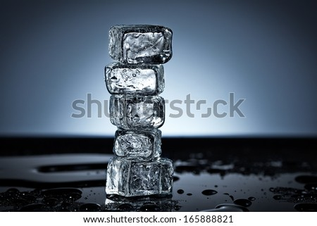 Five stacked ice cubes in wet black surface - stock photo