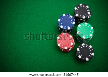 Five stacks of gambling chips on green felt background