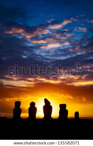 Five standing moais at sunset against orange sky - stock photo