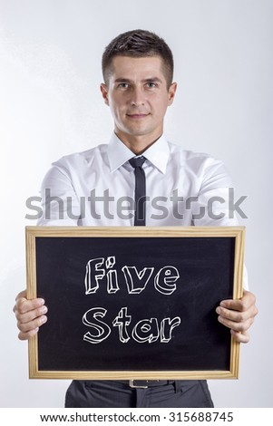 Five Star - Young businessman holding chalkboard with text - stock photo