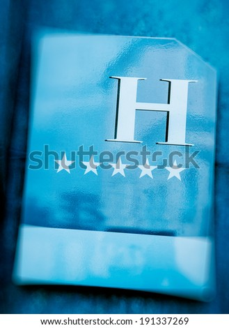 "Five stars hotel sign of a modern luxury worldwide network hotel. Tilt shift lens used to accent the five stars and word ""hotel"" - stock photo"