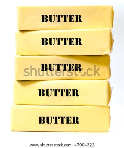 Five sticks of yellow butter stacked on top of each other, slightly angled on white background. - stock photo