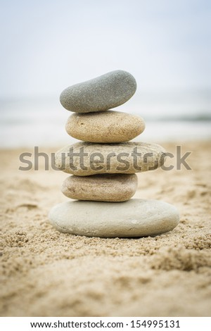 Five stones balanced on top of eachother on a sandy beach - stock photo