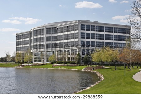 Five story office building with lake in suburbs - stock photo