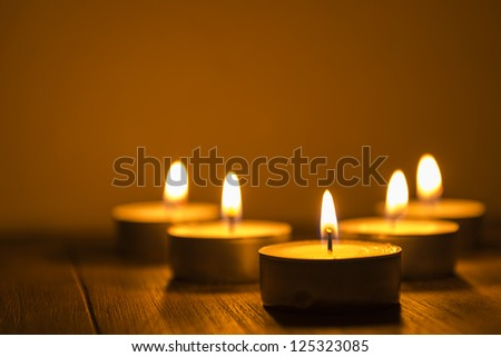 five tea lights on a table, shallow depth of field - stock photo