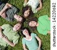 Five teens lay in grass - stock photo