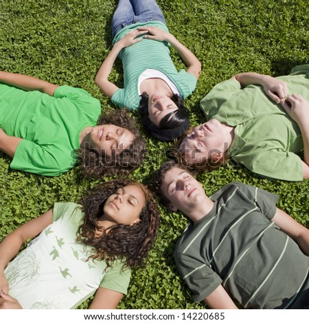 Five teens lay in grass