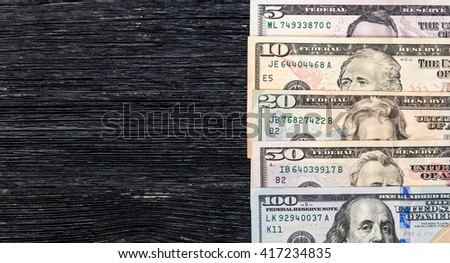 Five, ten, twenty, fifty and one hundred dollar bills on wooden background