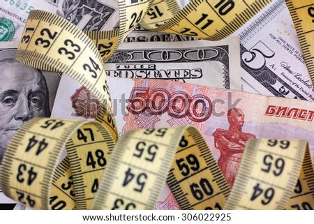 Five thousand rubles with yellow tape measure on dollar banknotes. Close up. - stock photo