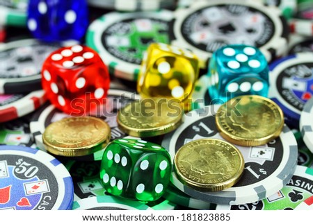 Five translucent colored dice laying on a pile of gambling chips of various denominations., with some gold coins also lying on the gambling chips  - stock photo
