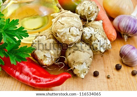 Five tubers of Jerusalem artichoke, garlic, onion, carrot, parsley, red pepper, peas sweet pepper and a bottle of vegetable oil on a wooden board - stock photo