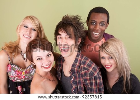 Five urban dressed teens laugh towards the camera in front of a green studio wall. - stock photo