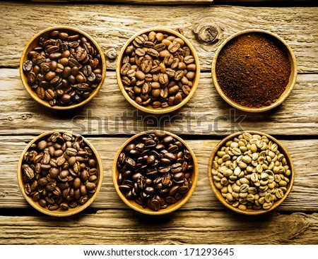 Five varieties of coffee beans and ground powder is separate dishes showing the different strengths and colour of the beans from raw through medium to full roast on a weathered driftwood background - stock photo