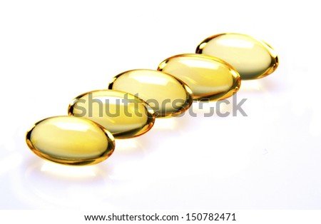 Five vitamin E capsules lined up in a row on white background - stock photo