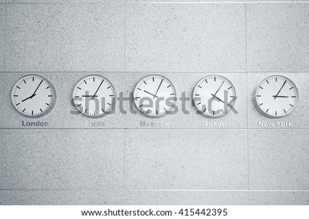 Five wall clocks showing time in different capitals of the world. - stock photo