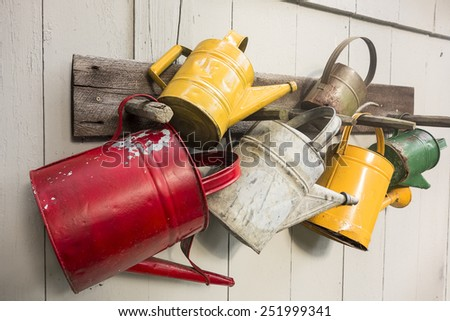 Five watering cans nailed to a shed wall form a display of rural paraphernalia. - stock photo
