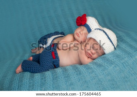Five week old sleeping boy and girl fraternal twin newborn babies. They are wearing crocheted sailor outfits. One baby is lying on her stomach and the other is propped on top of her sister. - stock photo